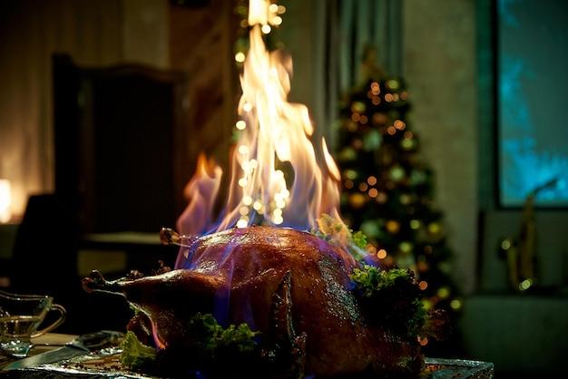 Dinde cuite au four sur un plateau dans une pièce faiblement éclairée.