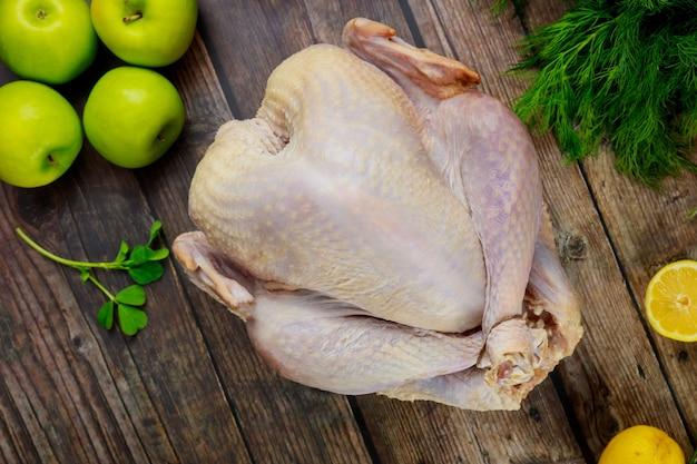 Dinde entière crue biologique sur table de cuisine en bois. vue de dessus.
