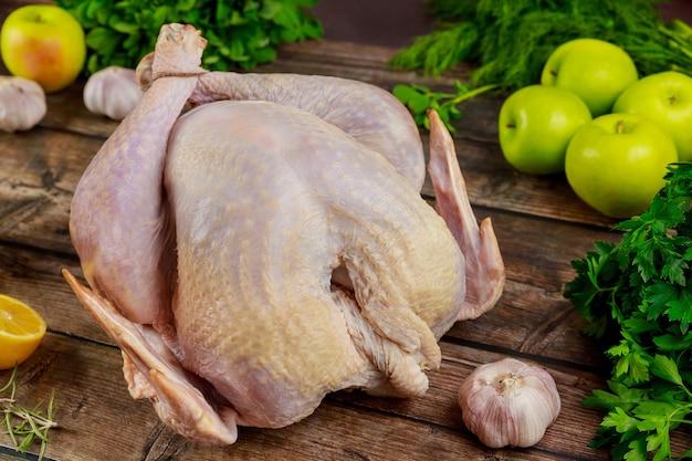 Dinde entière crue biologique sur table de cuisine en bois.