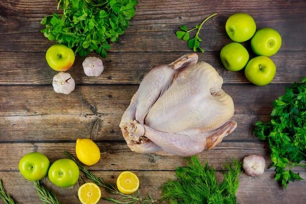 Dinde non cuite avec des ingrédients de cuisson et des épices sur une surface en bois.