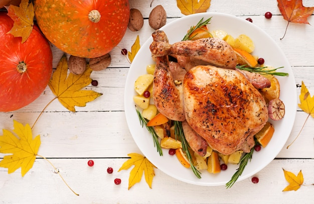 Dinde rôtie garnie de canneberges sur une table de style rustique décorée de citrouilles, d'orange, de pommes et de feuilles d'automne.