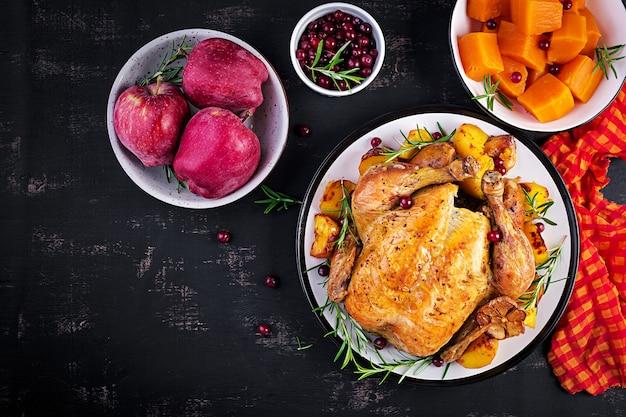 Dinde rôtie garnie de canneberges sur une table de style rustique décorée de feuilles d'automne. jour de thanksgiving. poulet au four. vue de dessus