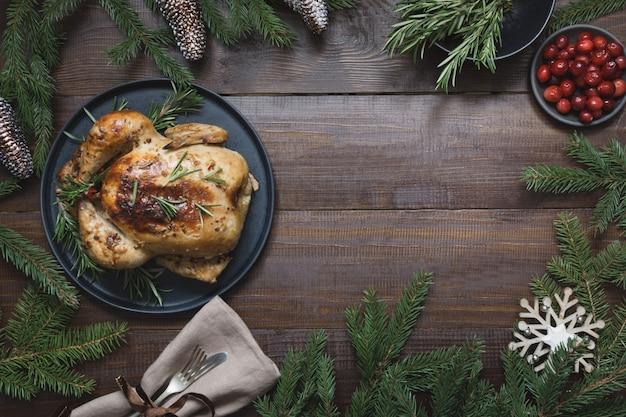 Dinde rôtie de noël traditionnel avec des épices et du romarin sur fond de table en bois. vue de dessus.