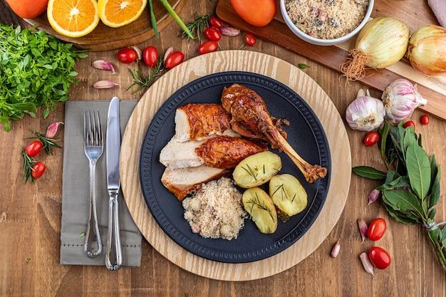 Dinde rôtie servie sur une assiette avec farofa, chapelure et pommes de terre bouillies