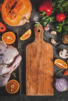 Dîner de cuisine pour noël, thanksgiving. les ingrédients traditionnels de l'automne sont les légumes, la citrouille, les champignons, le poulet ou la dinde, les herbes fraîches et les épices. table sombre, vue de dessus
