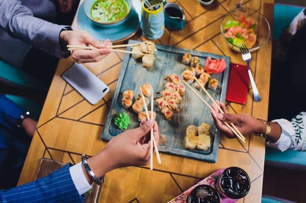 Un dîner en famille tenant les baguettes sur le plateau de sushis. mise à plat, vue de dessus.