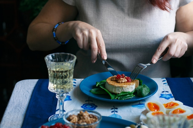 Un dîner gastronomique: camembert grillé, un verre de vin et diverses entrées.