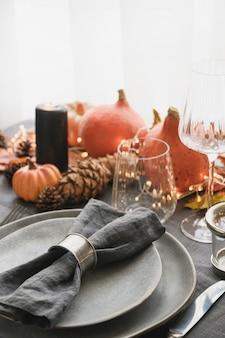 Dîner d'halloween et de thanksgiving décoré de feuilles mortes citrouilles épices assiette grise