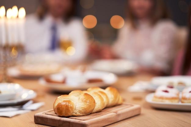 Dîner de hanoucca. famille réunie autour de la table avec des plats traditionnels