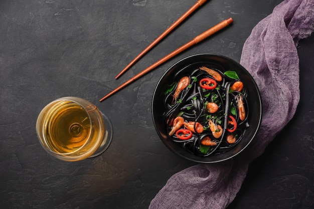 Dîner japonais moderne, cuisine méditerranéenne, pâtes spaghetti à l'encre de seiche noire avec fruits de mer, huile d'olive et basilic, sur une table rouillée foncée.