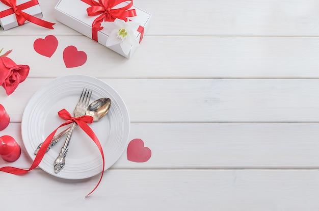 Dîner le jour de la saint-valentin. publicité de menu de restaurant. assiette avec des couverts avec des coeurs et des cadeaux avec une rose rouge sur un fond en bois blanc avec espace copie. dîner de vacances romantique.