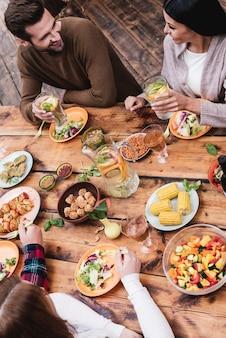 Dîner avec les meilleurs amis. vue de dessus de quatre personnes en train de dîner ensemble