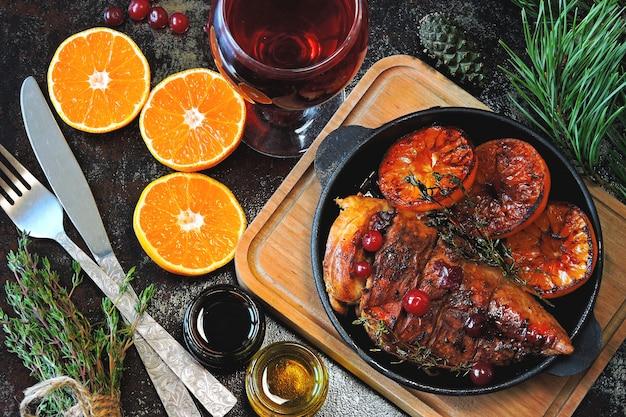 Dîner de noël. poitrine de poulet cuite au four avec mandarines et canneberges. branches d'arbres de noël et un verre de vin.