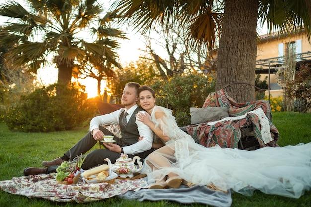 Dîner Des Nouveaux Mariés Sur La Pelouse Au Coucher Du Soleil.un Couple S'assoit Et Boit Du Thé Au Coucher Du Soleil En France Photo Premium