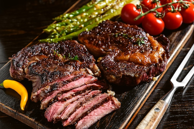 Dîner pour deux délicieux steaks juteux, asperges au parmesan et légumes.