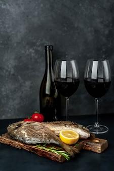 Dîner pour deux - poisson dorado grillé servi sur une planche à découper avec des épices et une bouteille de vin, verres sur un fond de pierre