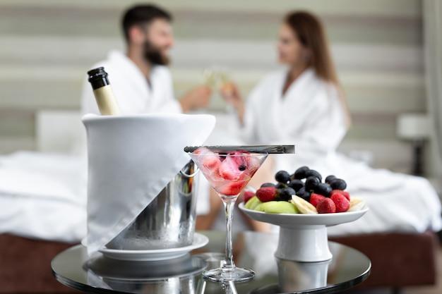 Dîner romantique à l'hôtel de baies et fruits pour un jeune couple qui boit du champagne au lit.