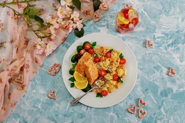 Dîner romantique pâtes en forme de coeur, saumon et légumes.