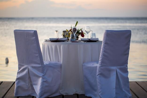 Dîner romantique sur la plage au coucher du soleil