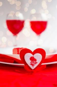 Dîner romantique pour la saint valentin. coeur avec une fourchette et des assiettes blanches sur fond clair