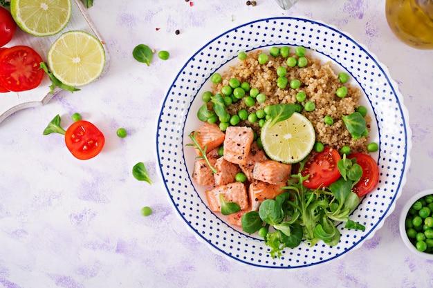 Dîner sain. tranches de saumon grillé, quinoa, pois verts, tomate, citron vert et feuilles de laitue. mise à plat.