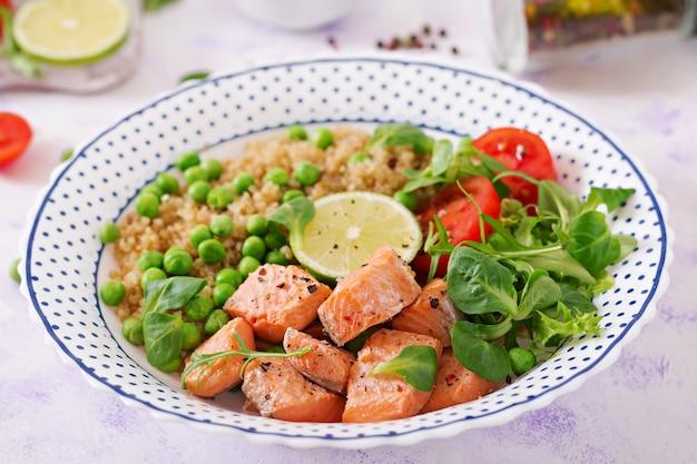 Dîner sain. tranches de saumon grillé, quinoa, pois verts, tomates, citron vert et laitue