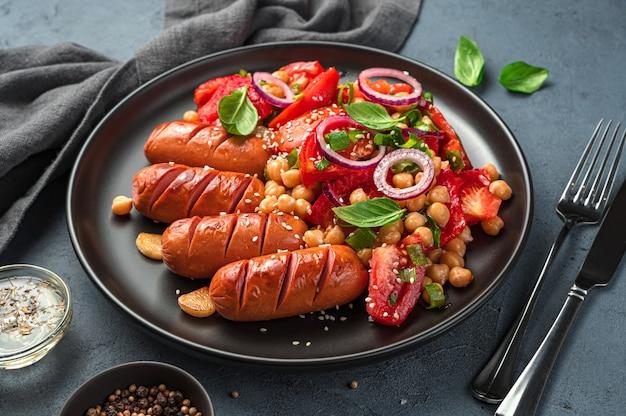 Dîner avec salade de légumes aux pois chiches et saucisses frites en gros plan