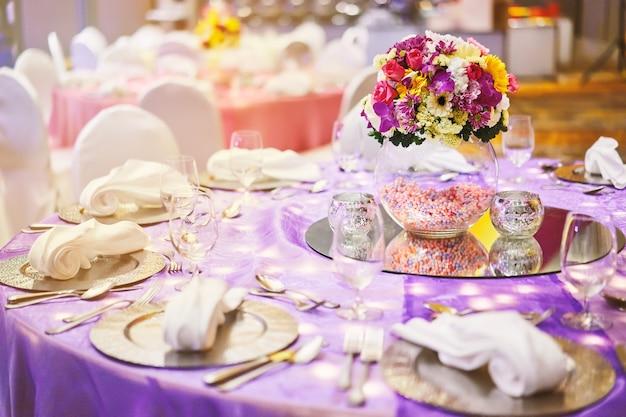 Dîner table avec un vase en verre de décoration de bouquet de fleurs