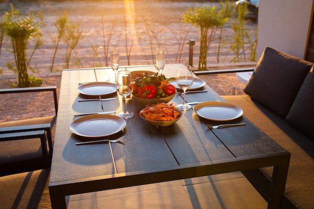 Dîner terrasse pour la famille vin avec miaou au coucher du soleil nourriture sur la terrasse au coucher du soleil