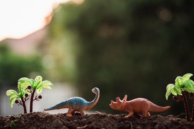 Dinosaure dans le coucher de soleil dans la jungle