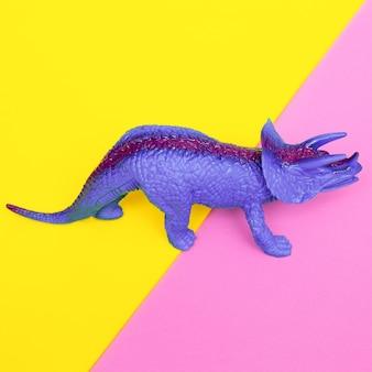 Dinosaure en plastique sur fond coloré. art minimal à plat.
