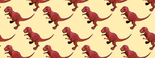 Dinosaure en plastique jouet sur un fond coloré. concept de modèle sans couture pour la texture, le design, le papier peint, la décoration, le textile. bannière