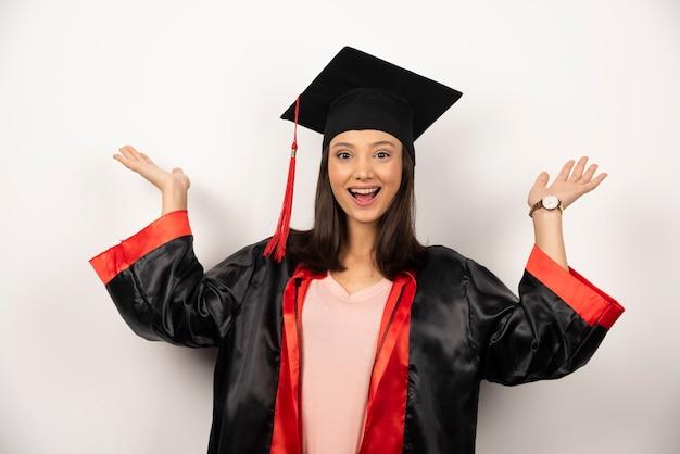 Diplômé frais en robe montrant ses mains sur fond blanc.