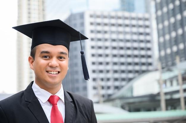 Diplômé heureux. heureux homme asiatique en robes de graduation détenant un diplôme en main sur la ville urbaine.