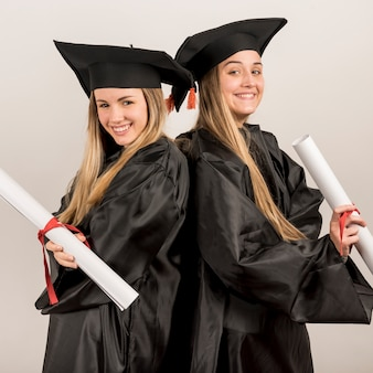 Diplômé moyen posant et souriant à la caméra