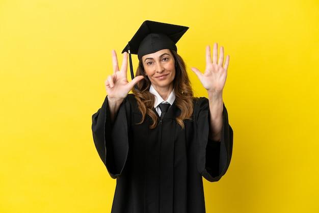 Diplômé de l'université d'âge moyen isolé sur fond jaune comptant huit avec les doigts