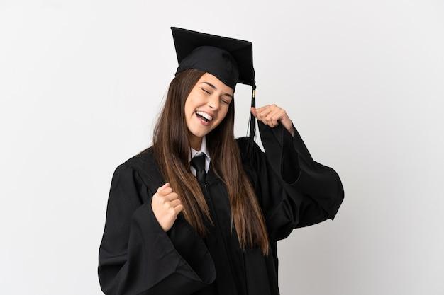 Diplômé de l'université brésilienne adolescent sur fond blanc isolé célébrant une victoire