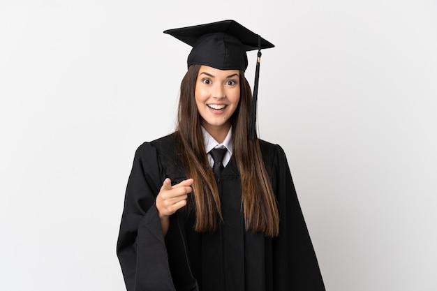 Diplômé de l'université brésilienne adolescent sur fond blanc isolé surpris et pointant vers l'avant