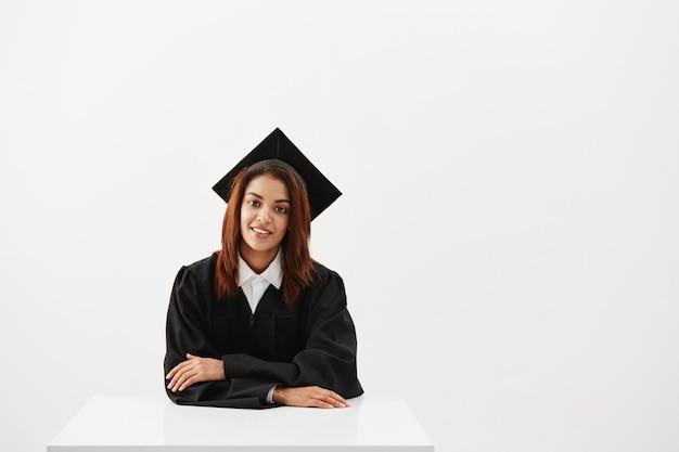 Diplômée africaine souriante assise. fond blanc. copiez l'espace.