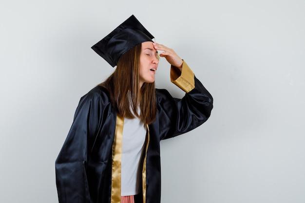 Diplômée féminine gardant la main sur la tête en robe académique et à la vue ennuyée, de face.
