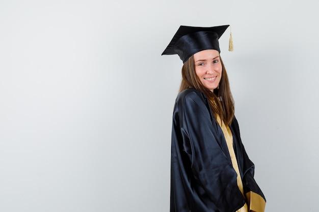 Diplômée féminine posant debout en tenue académique et à la recherche de plaisir. .