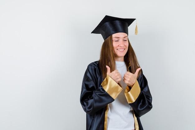 Diplômée montrant un double pouce en uniforme, des vêtements décontractés et à la chance, vue de face.