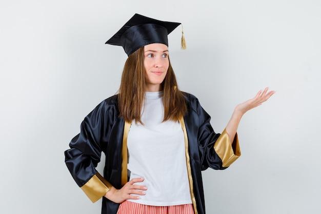 Diplômée montrant un geste de bienvenue en uniforme, vêtements décontractés et à la recherche concentrée. vue de face.