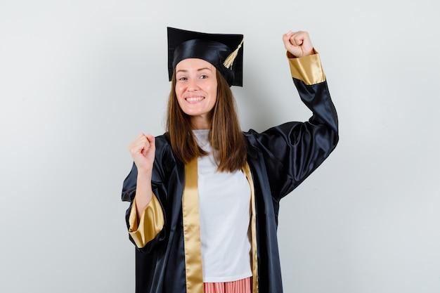 Diplômée montrant le geste du gagnant en tenue académique et à la joyeuse. vue de face.