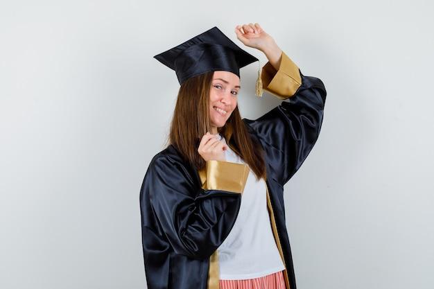 Diplômée montrant le geste gagnant en uniforme, vêtements décontractés et à la recherche de plaisir. vue de face.
