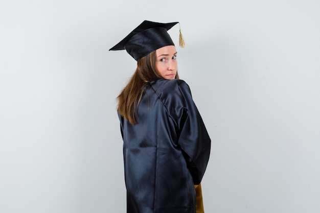 Diplômée en robe académique regardant la caméra par-dessus son épaule et à la jolie vue arrière.
