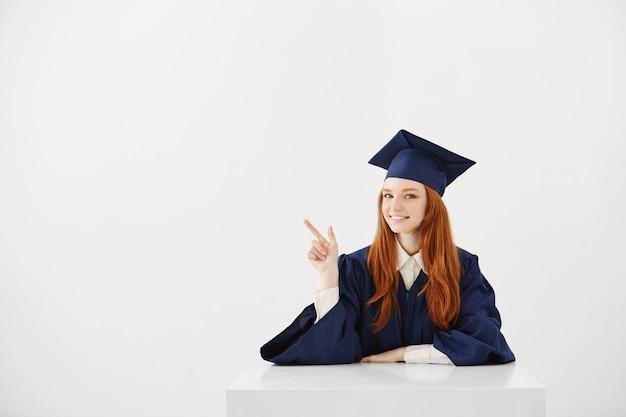 Diplômée de sexe féminin souriant pointant le doigt en position assise.