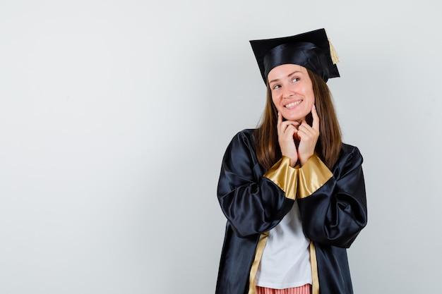 Diplômée en tenue académique en gardant les doigts sur les joues et à la rêveuse, vue de face.