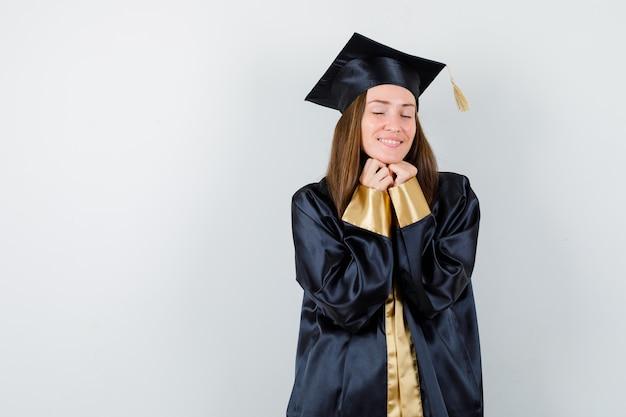 Diplômée en tenue académique, gardant les mains sous le menton et regardant heureux, vue de face.