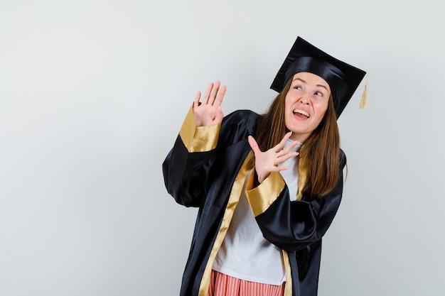 Diplômée en tenue académique montrant le geste d'arrêt et l'air effrayé, vue de face.